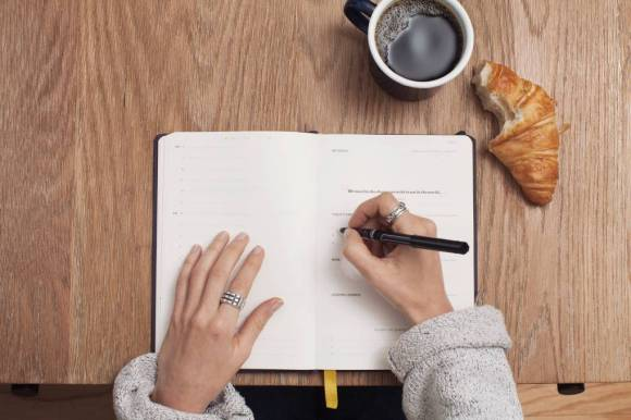 Person journaling on wooden table with mug of coffee and half-eaten croissant.