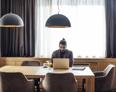 Man works on laptop sitting at spacious hotel table.