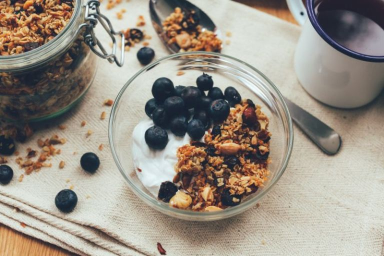 Greek yogurt, granola, and blueberries in a bowl, a great pre- or post-workout meal.
