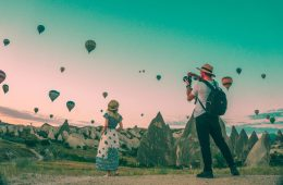 Two tourists look at a balloon-filled hazy sherbet sky and take pictures.