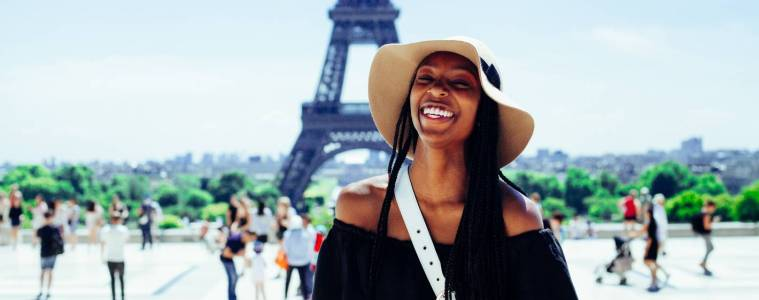 Smiling lady posing for picture in front of Eiffel Tower.