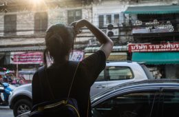 Woman traveler takes a photo with her iphone on busy urban street