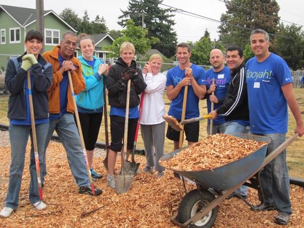 People standing outside with shovels and wood chips while volunteering, one of many team building activities for companies and corporations