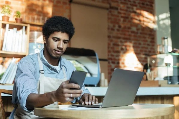 person using a laptop and a smartphone to review small business website design examples