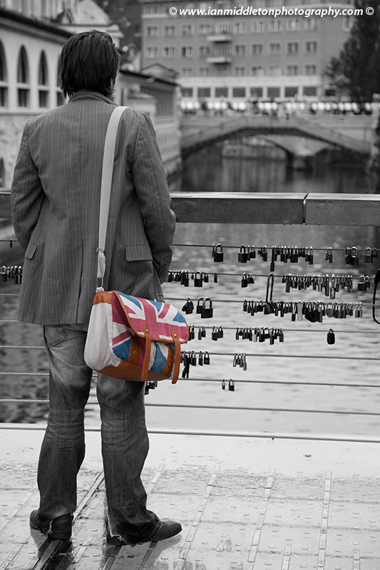British man with union jack flag bag standing on The Butchers' Bridge looking over the Ljubljanica river towards the Trznica (market) Triple Bridge on a rainy day in Ljubljana, Slovenia. The wire fence on the bridge is covered with padlocks put there by locals and tourists. All this region was designed by Slovenia's most celebrated architect, Joze Plecnik.