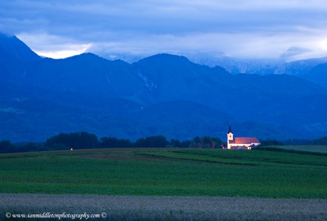 The church of Saint Peter lit at dawn and sitting in the shadow of the Kamnik Alps. This complex also contains a castle, a baroque church, a parsonage, a cemetery and a fairly large stable.