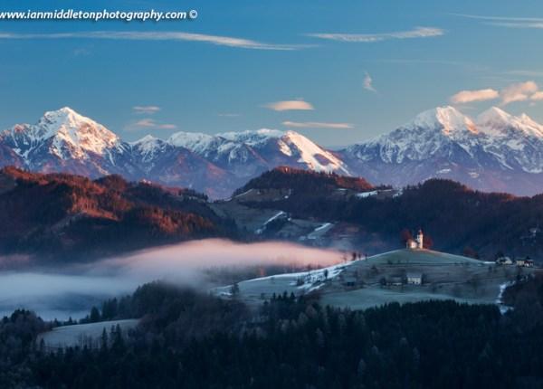 View at sunrise in winter from Rantovše hill across to Sveti Tomaz nad Praprotnim (church of Saint Thomas) and the Kamnik Alps, Slovenia.