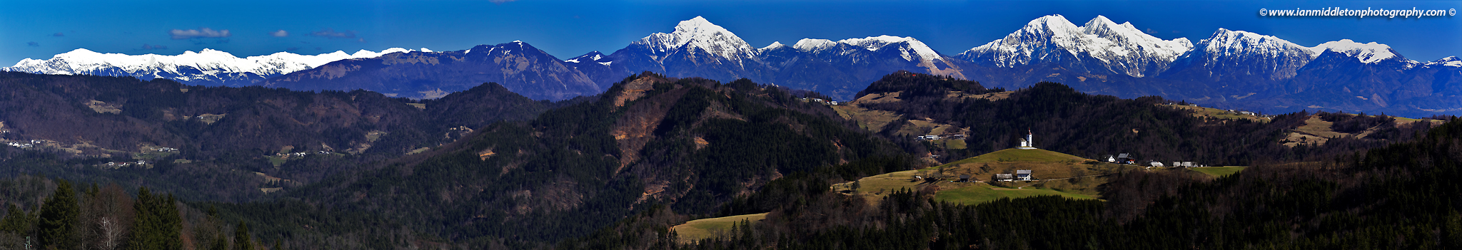 View across to Sveti Tomaz nad Praprotnim (church of Saint Thomas) in the Skofja Loka hills with the snowcapped Kamnik Alps in the background, Slovenia.