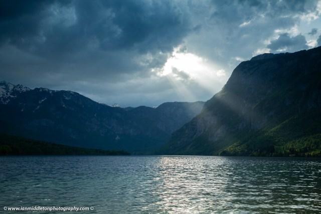 Sunlight breaking through clouds over the Julian Alps at Lake Bohinj, Triglav National Park, Slovenia