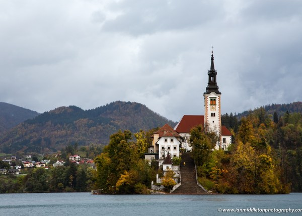 Tourist walking up the steps of Lake Bled's island church on a rainy autumn morning, Slovenia.