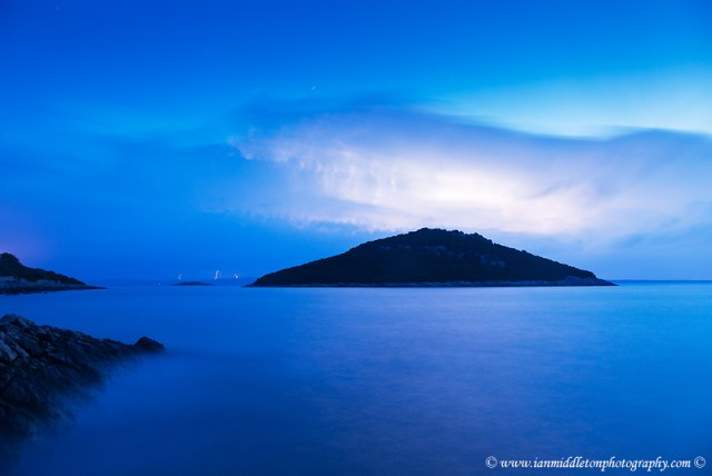 Lightning at dawn over the two small islands of Veli Osir and Mali Osir on Losinj Island, Adriatic Sea, Croatia. Photographed from Zaosiri beach near the village of Cunski, the main storm belt was primarily over the Istra peninsula but Losinj got the edge of it during the night. This was photographed as the storm moved southeast away from the Island.