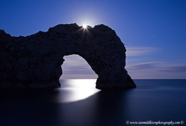 Durdle Door in the moonlight, Dorset, England. Captured late evening as the moonlight flooded through the rock's archway. The long exposure has also produced some nice star trails to the right of the arch. Durdle door is one of the many stunning locations to visit on the Jurassic coast in southern England.
