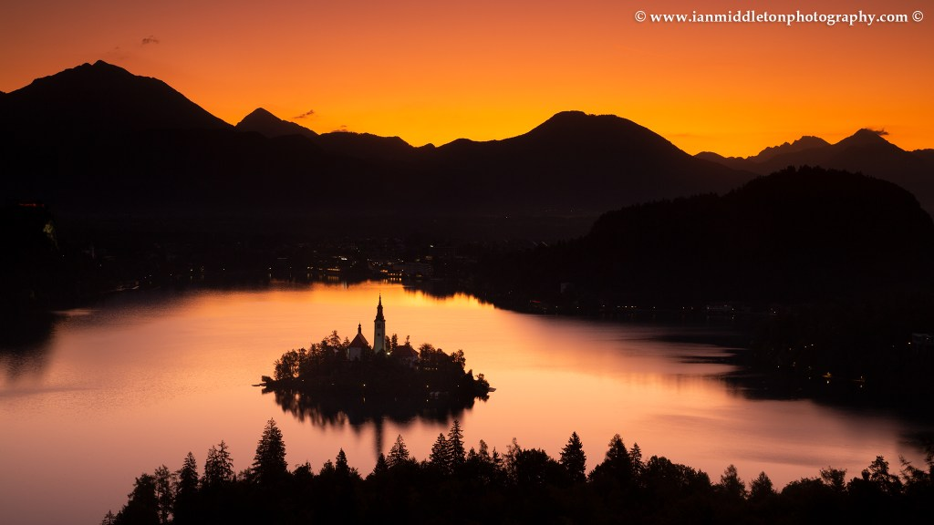 View across Lake Bled to the island church and clifftop castle from Ojstrica at sunrise, Slovenia.