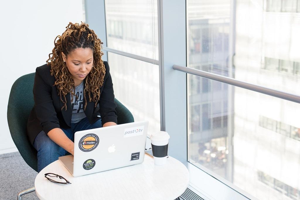 Mulher em uma cadeira, utilizando notebook enquanto toma café e avalia sua reserva de emergência..