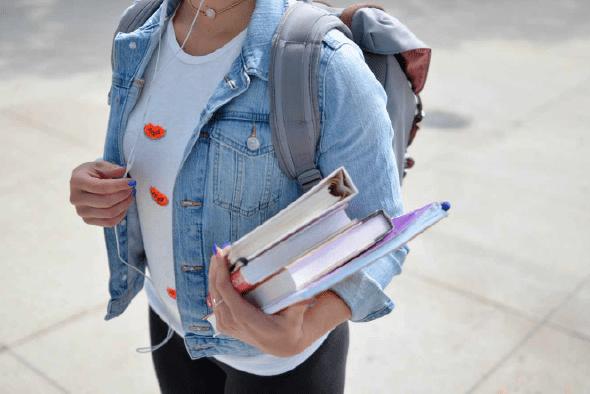 joven llevando libros y su mochila