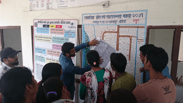 Practical Action Nepal, the Center for Social Development and Research and community members discuss the transfer of community maps to online maps © Wei Liu   IIASA