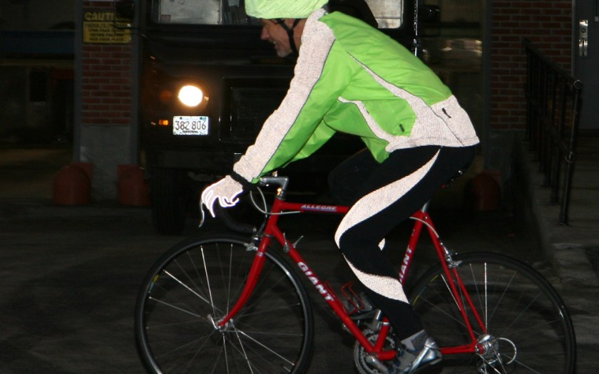A man in reflective clothing bicycles past a truck at night