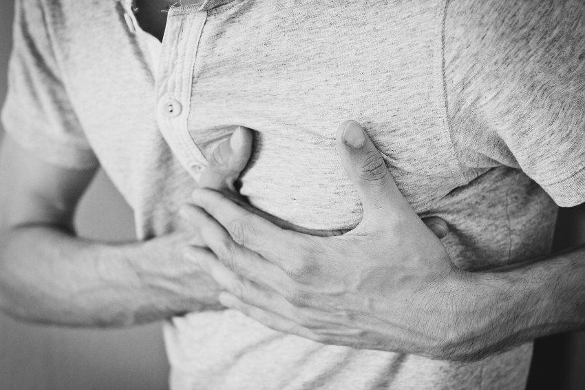 Pessoa com as mãos sobre o peito, indicando algum problema no coração.