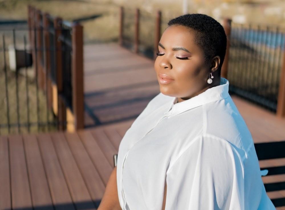 Mulher sentada ao ar livre realizando exercícios de respiração.