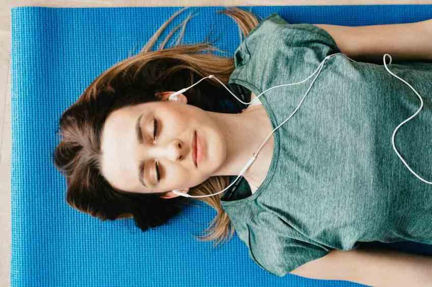 Mulher deitada de olhos fechados meditando, mostrando como controlar a falta de ar em casos relacionados à ansiedade.