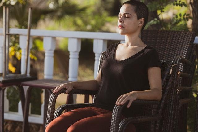 Mulher meditando sentada em uma cadeira ao ar livre, mostrando que é possível meditar corretamente em outras posições além da tradicional.