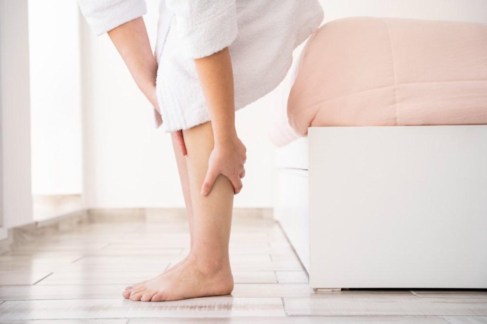mulher com varizes segurando a perna.