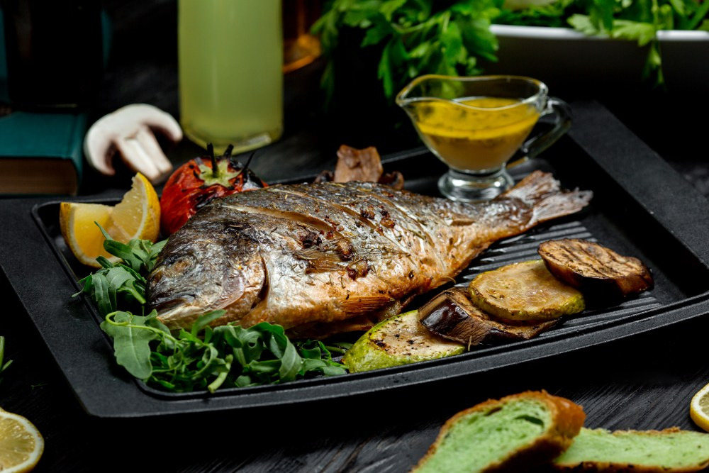 Um prato com um peixe frito, alguns legumes e uma ambientação ao fundo desfocada.