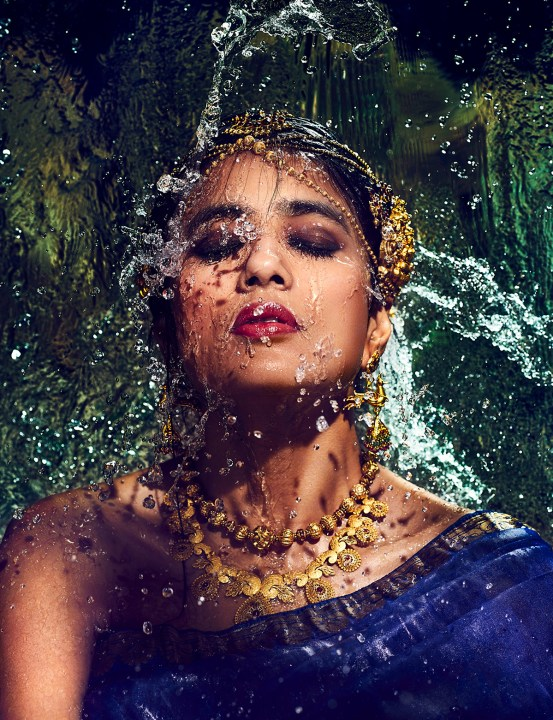 Water flows over the model dressed in a blue sari. She has gold jewelry on her neck, nose and head. Her makeup is flawless.