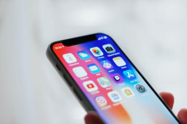 Pessoa segurando um smartphone com uma das mãos e vendo seus aplicativos na tela;