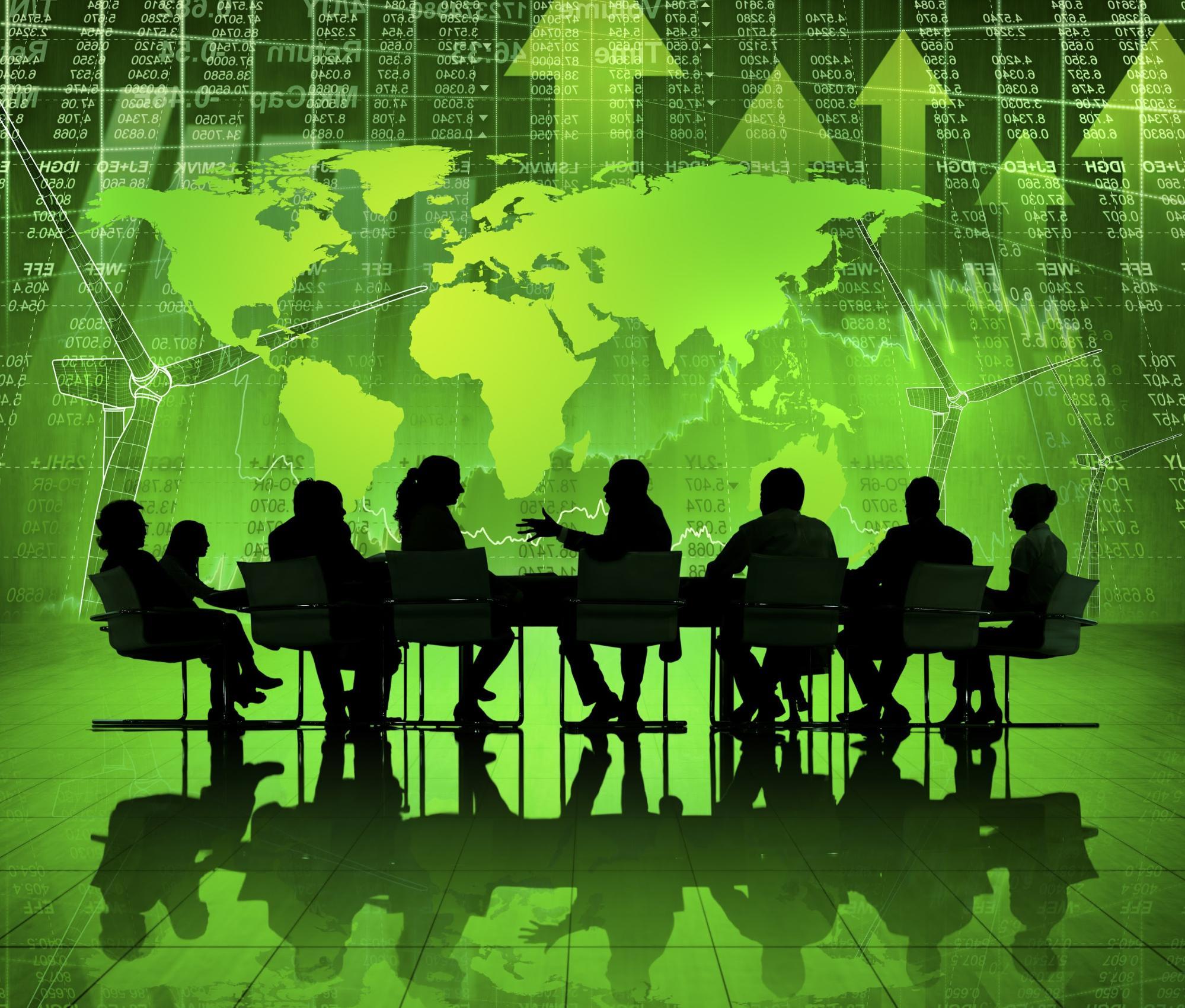 Imagem criada digitalmente, com a silhueta de pessoas em uma mesa de negócios. Ao fundo, em tons de verde, temos o mapa mundial sobreposto à uma tela com números e setas, visando ilustrar a temática do texto ' Tecnologia ambiental: como a tecnologia ajuda o planeta?