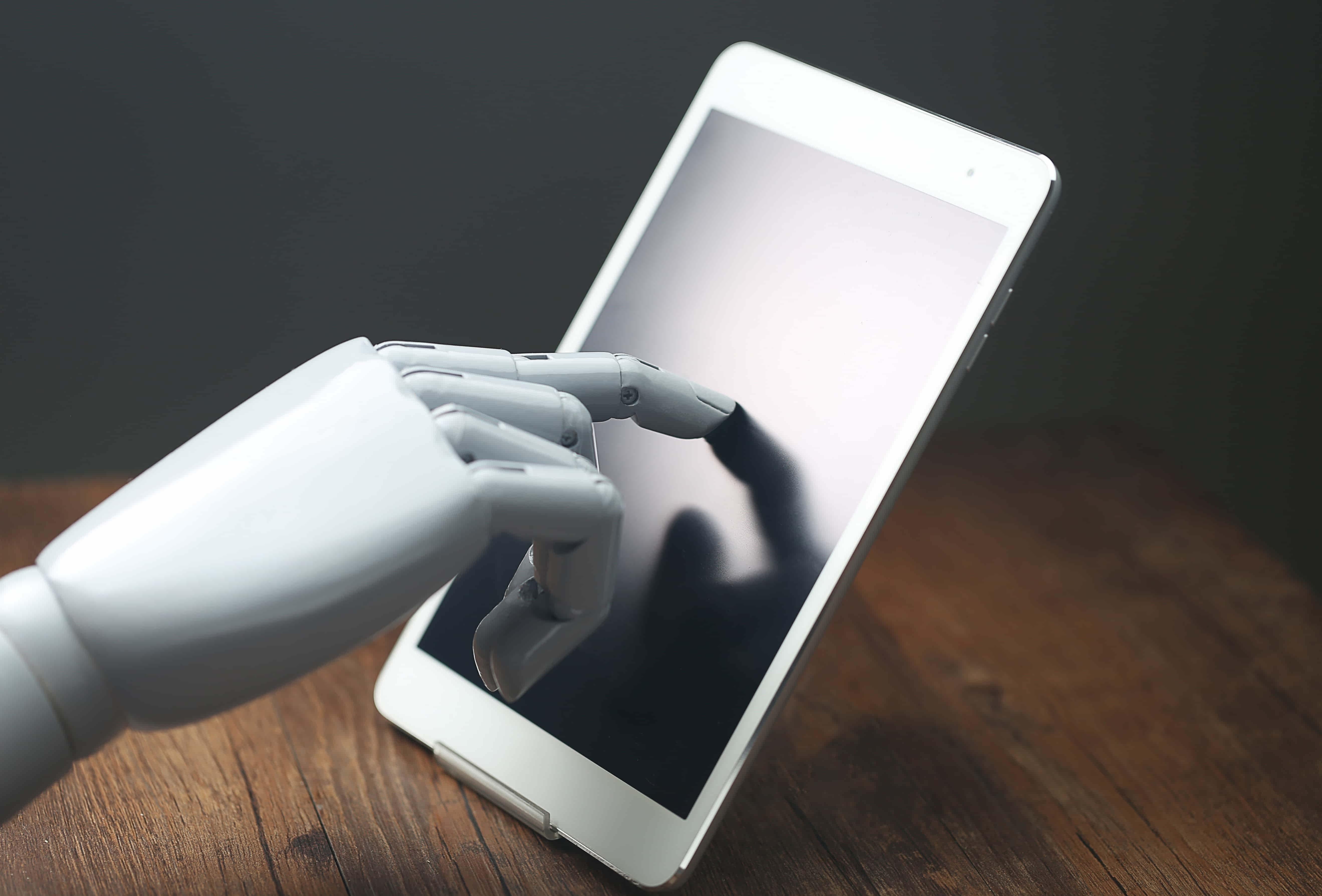 Composição criada digitalmente, em 3D, na qual vemos uma mão robótica tocando um smartphone, representando a importância da linguagem natural nas interações tecnológicas.