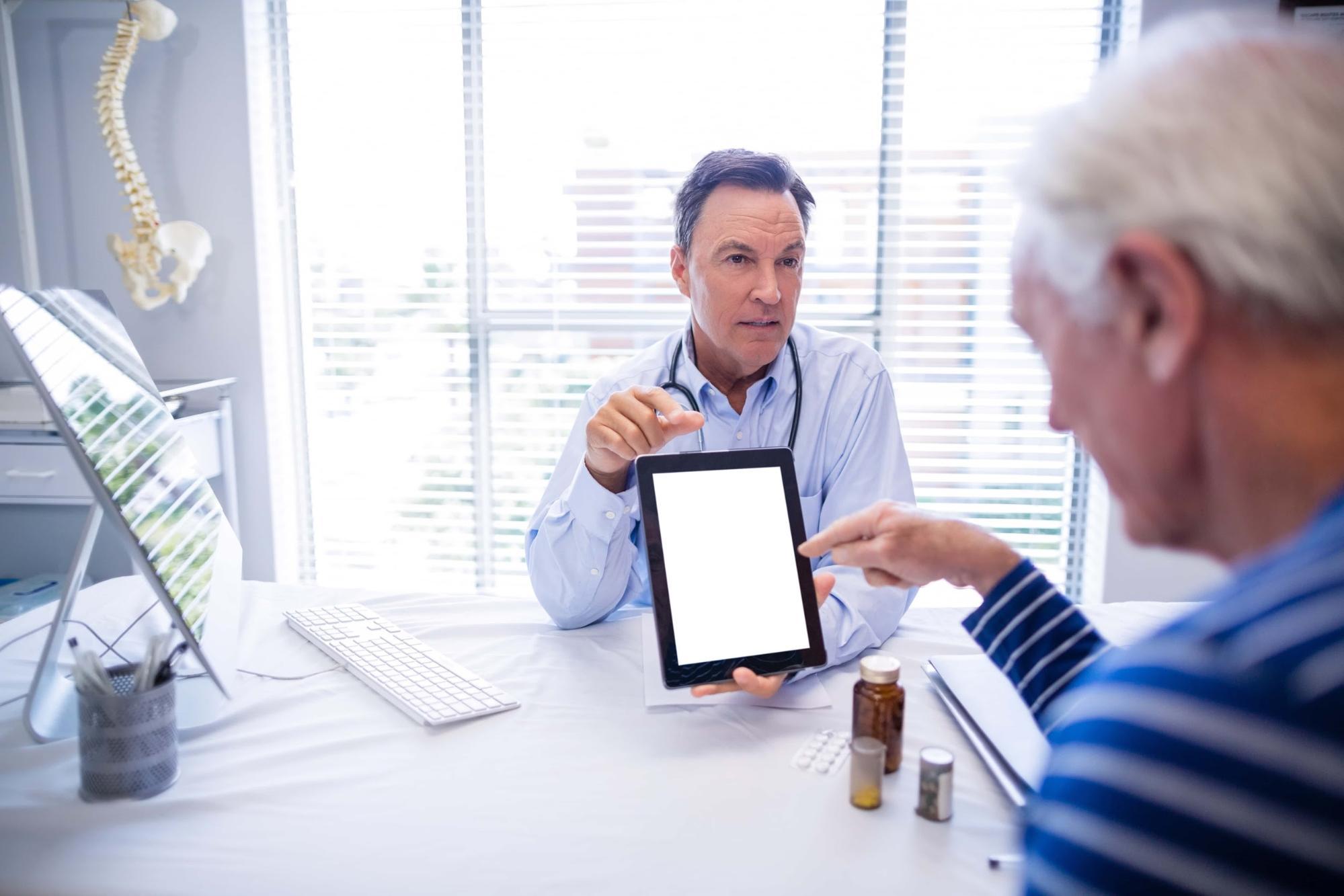 Foto de um médico apresentando informações ao seu paciente, por meio de um tablet. A imagem ilustra a importância de aliar saúde e tecnologia