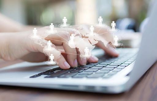 Mãos teclando em um laptop. Por cima das mãos uma imagem vetorizada representando pessoas conectadas ao redor do mundo.