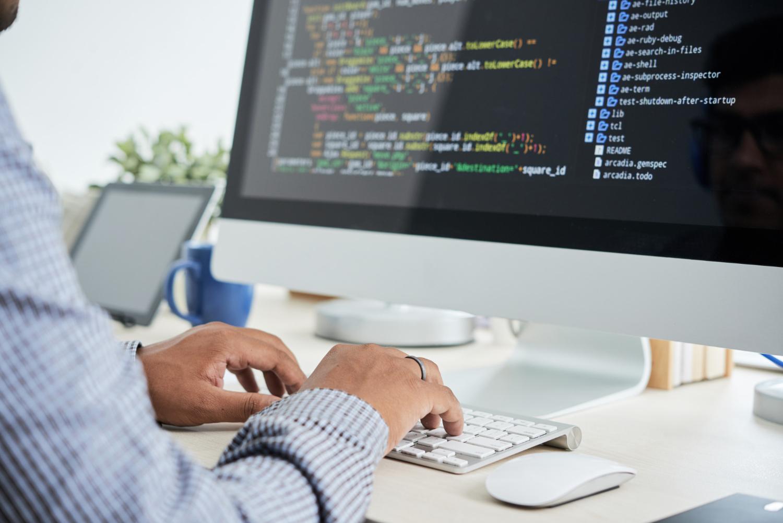Imagem de uma pessoa digitando em seu teclado e aparecendo códigos na tela do computador