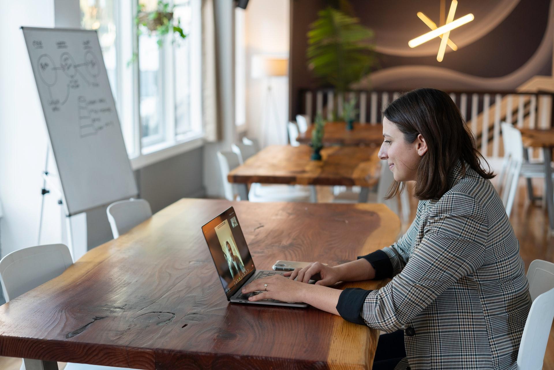 Mulher trabalhando olhando para a tela do notebook.