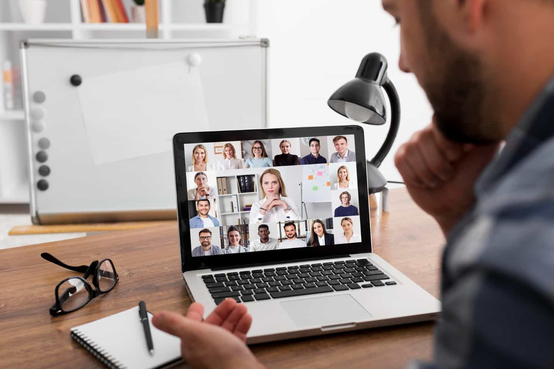 Homem olhando para tela do notebook, participando de reunião online.