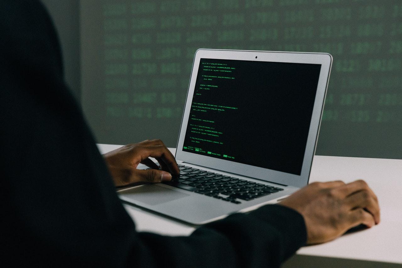 Notebook aberto com códigos de programação na tela sobre mesa branca. Pessoa de roupa preta mexendo no notebook. Ao fundo, parede onde estão sendo projetados códigos de programação.