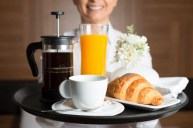 Room service is bringing breakfast with orange juice, croissant and french press coffee.