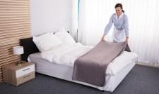 Housekeeper Making Bed In Hotel Room