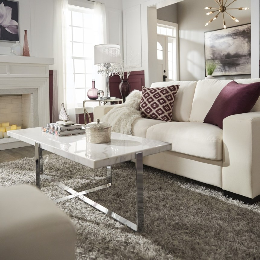 Glam designed living room with closeup view of white couch, purple pillows and marble cocktail table