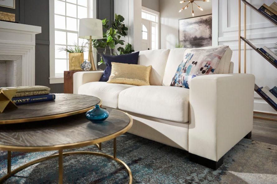 Modern design living room with up close view of white sofa, blue and gold pillows and nesting coffee table