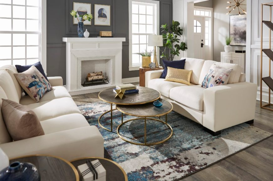 Modern designed living space with white couch, blue and gold pillows and nesting tables