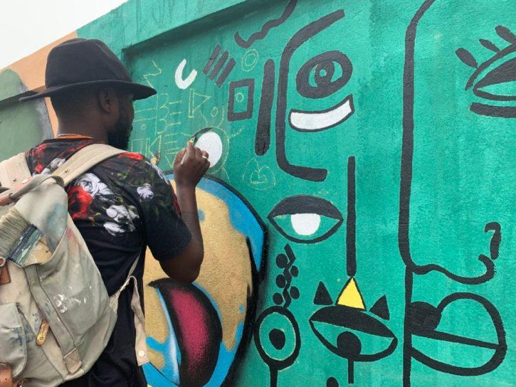 Un artiste graffeur peint sur une fresque murale durant le festival d'art urbain et de graffiti Effet Graff, qui met en valeur l'art urbain et le graffiti pour le rendre accessible à tous.