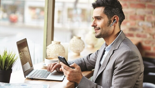 Man wearing Jabra Stealth using smartphone and laptop