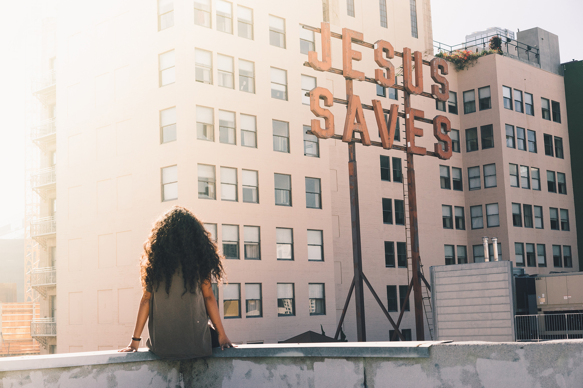 Woman gazing at a sign that reads 'Jesus Saves'.