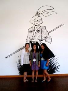 2011 Getty interns Yuiko Sugino, Alexa Kim, and Alyctra Matsushita, in front of a wall drawing by Stan Sakai.