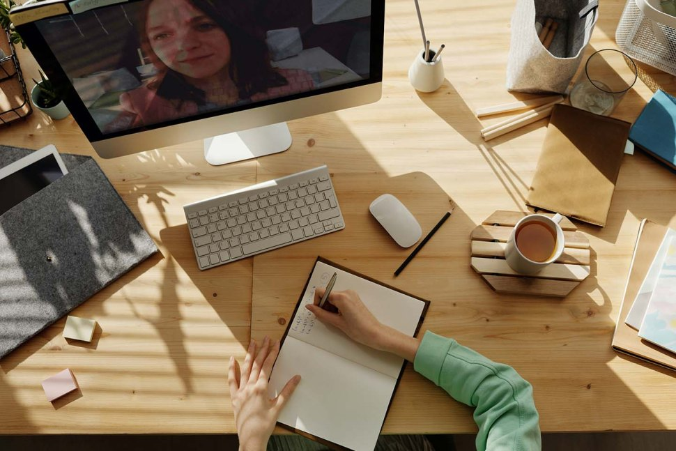 An image of  person writing n a note book on a desk. perhaps about 5 ways to keep your freelance collective happy!