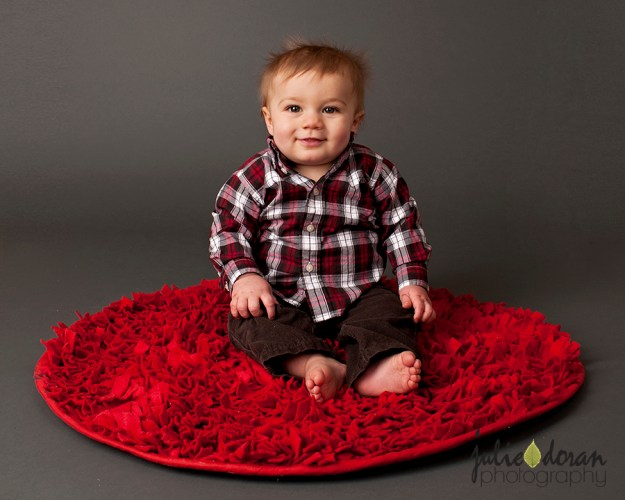 baby boy on red rug