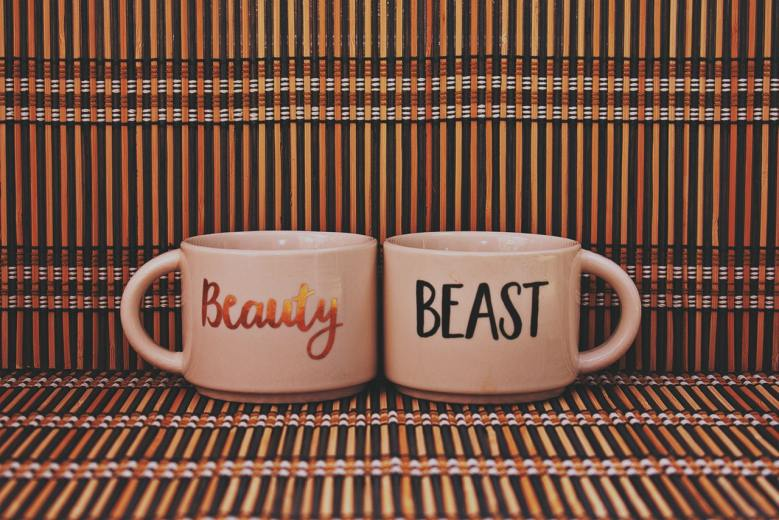 """A couples' mug with the words """"Beauty"""" and """"Beast"""" printed on them."""