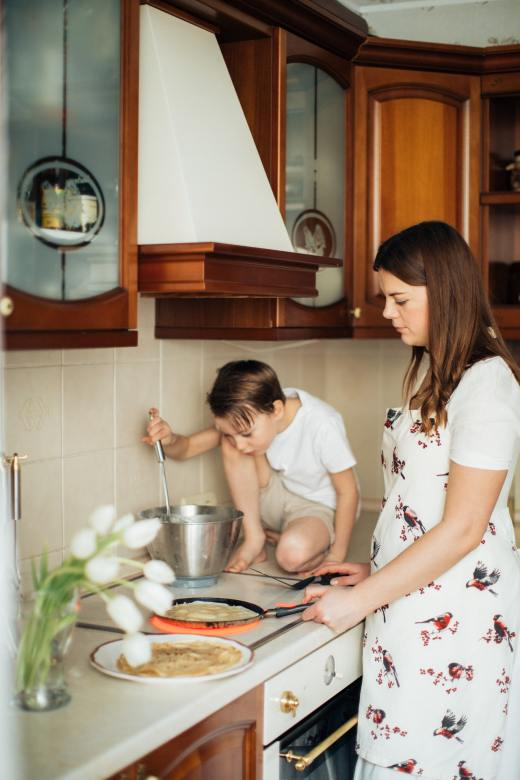 A mother and son cooking together in the kitchen